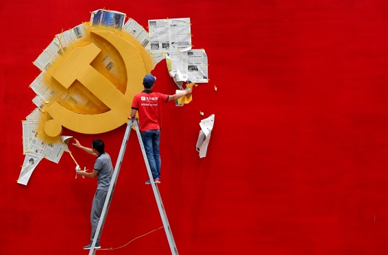 Workers peel papers off a wall as they re-paint the Chinese Communist Party flag on it at the Nanhu revolution memorial museum in Jiaxing, Zhejiang province May 21, 2014. REUTERS/Chance Chan (CHINA - Tags: POLITICS SOCIETY)